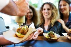 Tre härliga unga kvinnor som köper köttbullar på en matlastbil Royaltyfri Fotografi