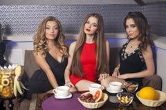Tre härliga unga kvinnor som kopplar av i en nattklubb fotografering för bildbyråer