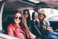 Tre härliga vänner för unga kvinnor har gyckel i nolla-bilen, som de går på en vägtur royaltyfri foto