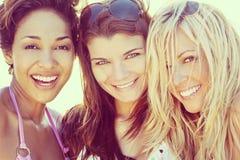 Tre härliga vänner för unga kvinnor som skrattar på stranden royaltyfria bilder