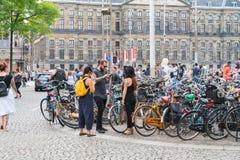 Tre höftpersoner som står bredvid cykeln, parkerar område genom att använda mobil Arkivfoton