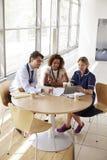 Tre höga sjukvårdarbetare i ett möte, hög vinkel arkivbild
