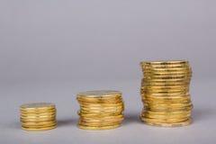 Tre högar av guld- mynt med en graf av tillväxt uppåt royaltyfria foton