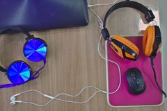 Tre hörlurar på skrivbordet Bärbara datorer och styrning royaltyfria foton