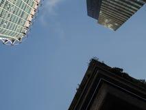 Tre hörn av moderna tornkvarter mot en blå himmel arkivfoto