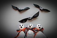 Tre halloween spökar och tre slagträn på grå bakgrund Arkivfoto