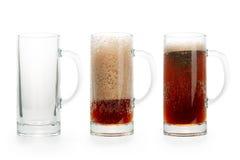 Tre halva liter av mörkt öl Tomt, halvfullt och mycket Arkivbild