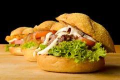 Tre hamburger appetitosi sulla tavola di legno Fotografia Stock