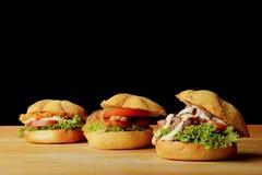 Tre hamburger appetitosi sulla tavola di legno Immagini Stock