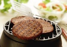 Tre hamburger su un barbecue Fotografia Stock