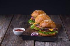 Tre hamburger succosi del manzo Immagine Stock