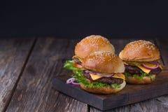 Tre hamburger succosi del manzo Fotografie Stock