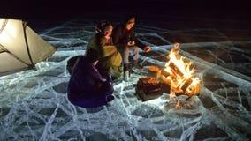 Tre handelsresande förbi brand som är höger på is på natten Tältplats på is Tältet står bredvid brand baikal lake Närliggande fin lager videofilmer