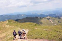 Tre handelsresandevänner promenerar slingorna av de Carpathian bergen, Rumänien Arkivfoto