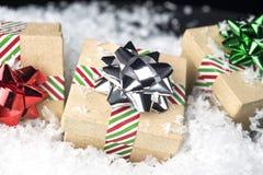 Tre hanno avvolto i regali di festa con gli archi brillanti ed il nastro che si siede la o Fotografia Stock Libera da Diritti