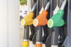 Tre hanno colorato le pompe del combustibile agganciate all'erogatore della benzina Immagini Stock