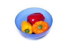 Tre hela spanska peppar av olika färger på brädet för att klippa i blått bowlar för mat Fotografering för Bildbyråer
