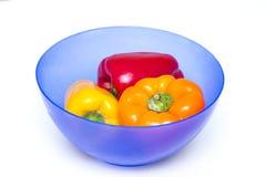 Tre hela spanska peppar av olika färger på brädet för att klippa i blått bowlar för mat Arkivbild