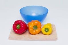 Tre hela spanska peppar av olika färger på brädet för att klippa och blått bowlar för mat Royaltyfri Foto