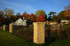 Tre hem, järnstaket, tegelstenstolpar, nedgångfärger Royaltyfria Foton