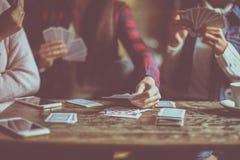 Tre hemmastadda spela kort för flickor tillsammans close upp Arkivfoto
