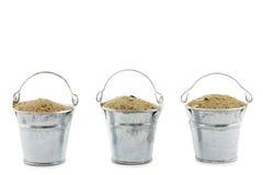 Tre hinkar som fylls med sand Arkivfoton