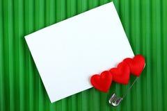 Tre hjärtor med ett kort till ett meddelande Royaltyfri Bild