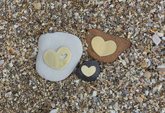 Tre hjärtor vaggar på på sand Arkivbilder