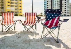 Tre hopfällbara strandstolar under skugga på stranden Royaltyfri Fotografi
