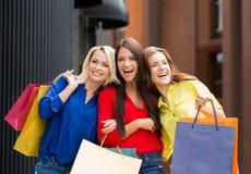 Tre härliga unga kvinnor som skrattar och är lyckliga Arkivbild