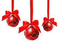 Tre hunging röda isolerade julbollar royaltyfri foto
