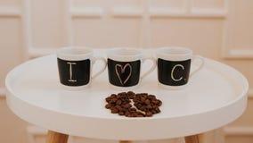 Tre identiska lilla kaffekoppar i rad som står på den vita runda trätabellen Med text älskar jag kaffe fotografering för bildbyråer