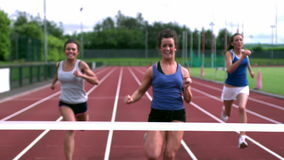 Tre idrottsman nen som kör in mot mållinjen lager videofilmer