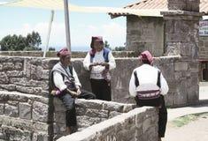 Tre iklädda traditionella dräkter för män som är specifika för den Taquile öregionen, en av dem som sticker en hatt Royaltyfri Bild