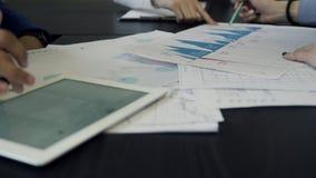 Tre impiegati che analizzano i documenti che si siedono allo scrittorio in ufficio stock footage