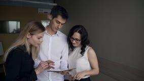 Tre impiegati di concetto guardano allo schermo digitale della compressa dentro l'ufficio archivi video