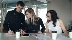 Tre impiegati nell'ufficio da confrontare le idee sull'affare proiettano stock footage
