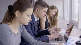 Tre impiegati stanno scrivendo con attenzione sui computer portatili vicino alla finestra archivi video