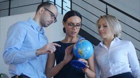 Tre insegnanti discutono qualcosa con il globo Immagini Stock Libere da Diritti