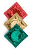 Tre involucri del preservativo nei colori dei semafori Fotografie Stock