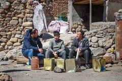 Tre iranska äldre män sitter och talar på gatan vaggar in byn Kandovan iran Royaltyfria Foton