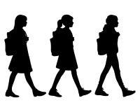 Tre isolerad kontur av flickor som går till skolan Fotografering för Bildbyråer
