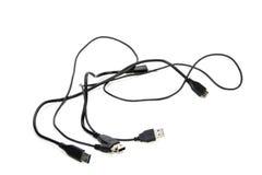 Tre isolerade svart flätade samman USB kablar på vit Arkivfoton