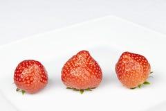 Tre jordgubbar på en platta Arkivbilder