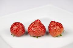 Tre jordgubbar på en platta Royaltyfri Bild