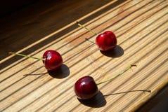 Tre körsbärsröda bär på en träbakgrund royaltyfria foton