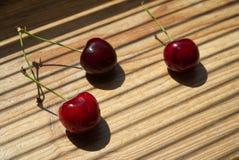 Tre körsbärsröda bär på en träbakgrund royaltyfri bild