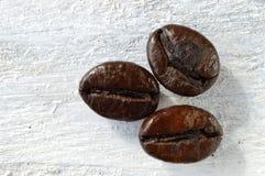 Tre kaffebönor på en vit trätabell Makro arkivbilder