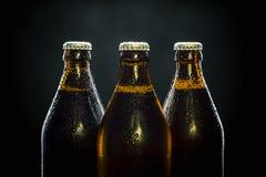 Tre kalla ölflaskor på svart arkivbilder