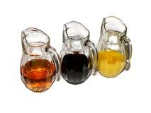 Tre kannor med kulöra fruktsafter Arkivfoton